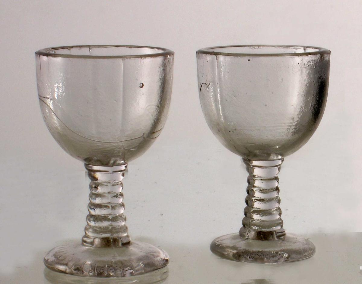 Stett med horisontale riller, rundt beger i tykt glass  med støperenner som deler det i to. En stripe i den ene halvdel.