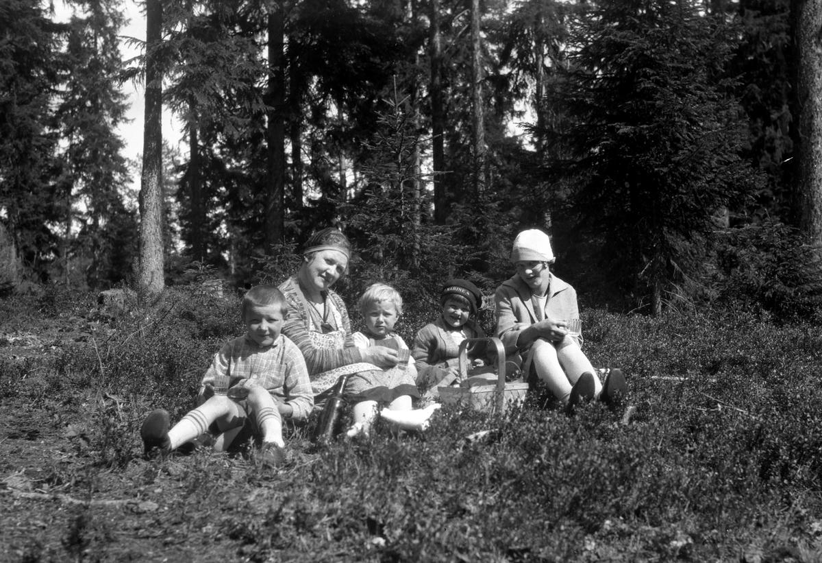 Kvinne med fire barn sitter i skogen.