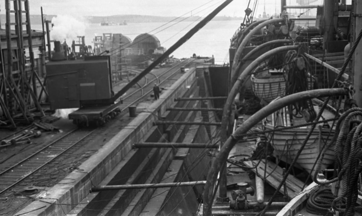 Kranen på kaien ved tørrdokken. Halifax skipsverft. Suderøy i tørrdokk under utrustning før avgang til fangstfeltet. Verftområdet i bakgrunnen.