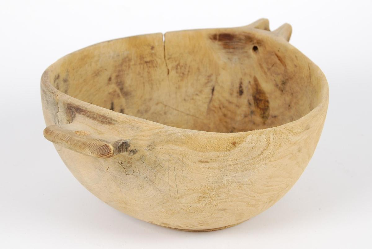 Trøys av tre. Tilnærmet rund/oval i formen. Åpen halsirkelformet tut med liten rund åpning. Håndtak med hull.