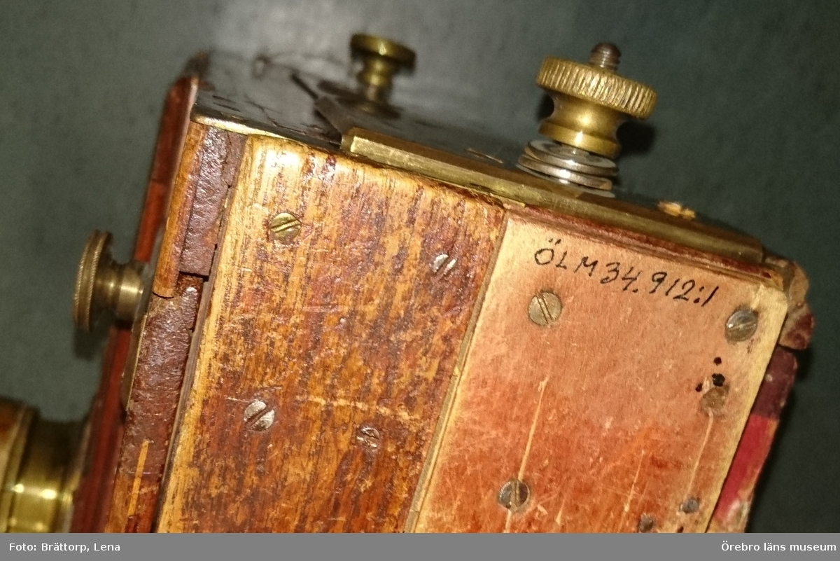 Kamera med stativ och skynke från 1890-talet. 1) Kamera för 18 x 12 cm glasplåtar av trä med bälg av klistrat och pressat linne. Kameran brunbetsad, bälgen grön med bruna hörn. Bälgen vrids ut med hjälp av mässingsrattar på refflade spår. Baksidan utfällbar med matt glasskiva. Bottenplattan har ett gängat hål till stativet. En bärrem av läder på ovansidan.  Objektivet 4,2 cm höjd, dia: 5,4 cm av mässing. Märkt: Anastigmat No 178699 serie 3 Dagor FF2,40 mm 6,8 Pat CP Goertz Berlin. Mått: 345 x 280 x 120 mm. 2) Stativet av trä. Går att förlänga. Mått: Längd: 560 mm. Diam: 120 mm. 3) Duk av bomull, svart. Dubbelt, maskinsytt. Springa för objektivet: 90 mm. Mått: 1280 x 1270 mm. Inköpt från Gittan Lindskog, Örebro. Kameran har tillhört Sam Lindskog, Örebro, och var en gåva av hans sista arbetgivare, Sven Svensson, Linköping 1898.