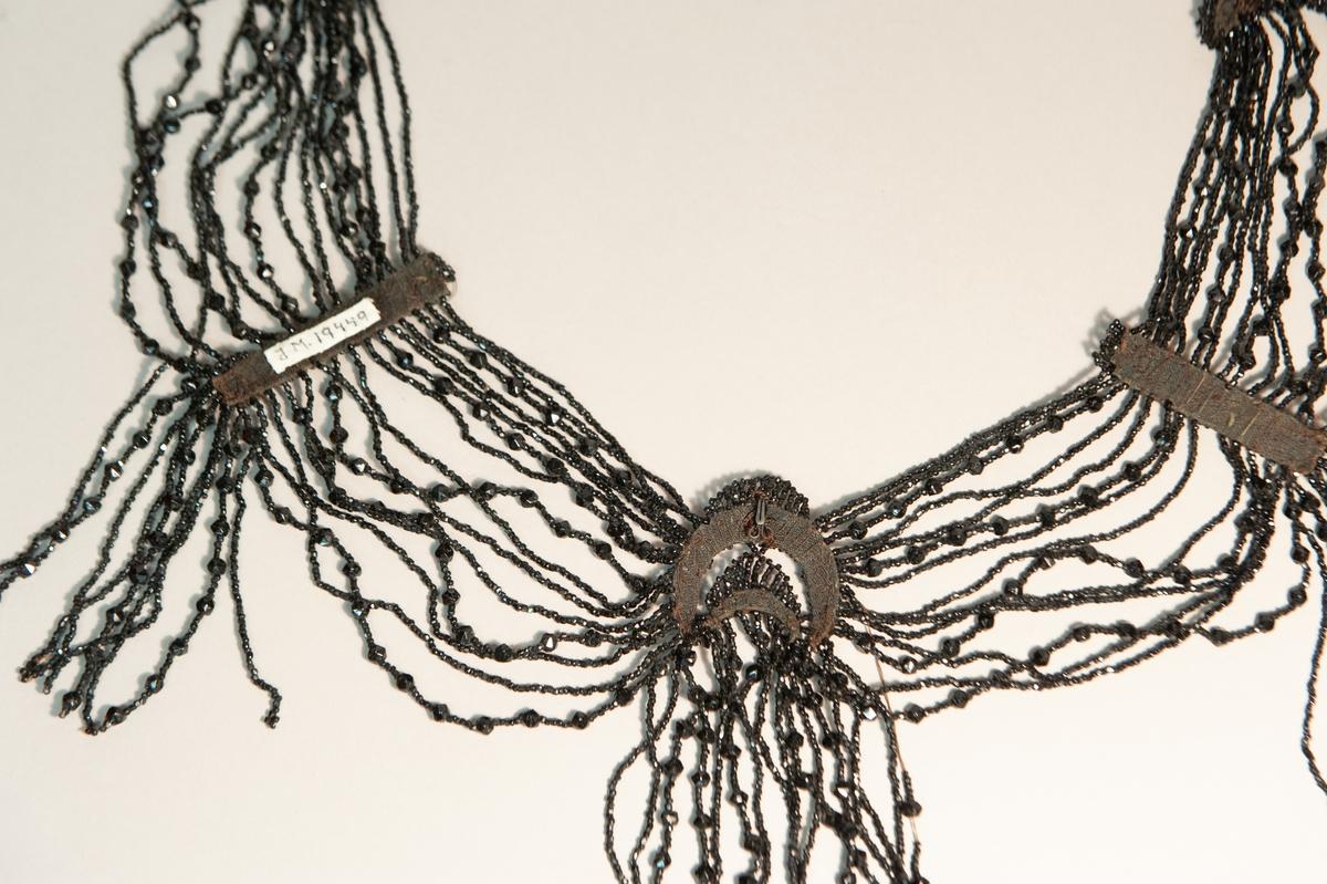 Ett klänningsgarnityr med pärlrader av stenkolspärlor uppträdda på silkestråd. Tre hakar finns på baksidan för att kunna fästa pärlraderna i plagget.