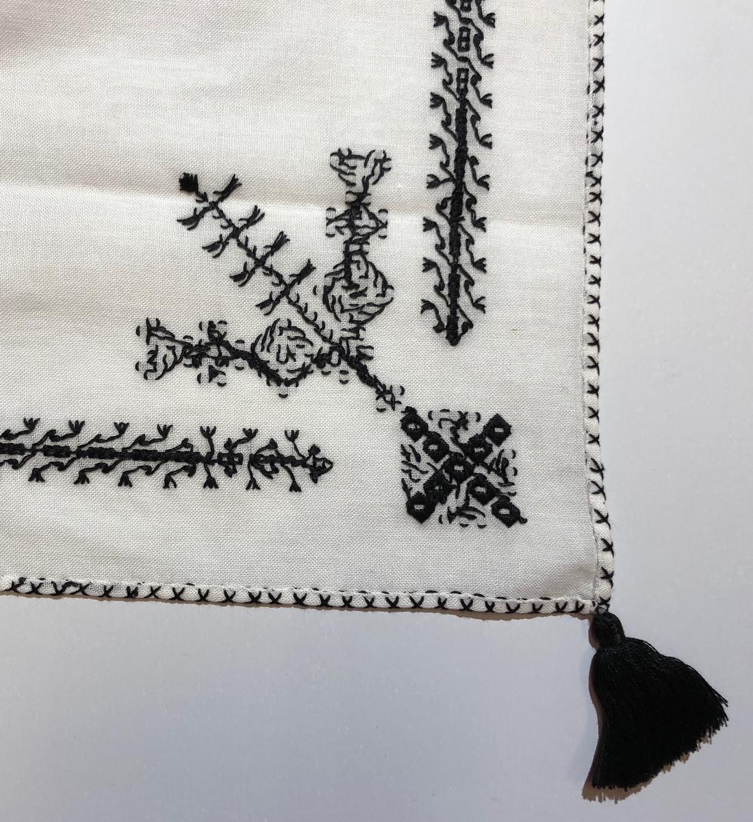 Halsklädet har ett enkelt broderi med en bård mellan ryggsnibb och framsnibbar. På ryggsnibben finns en fyrkant och en enkel dekoration. På framsnibbarna en halv fyrkant.