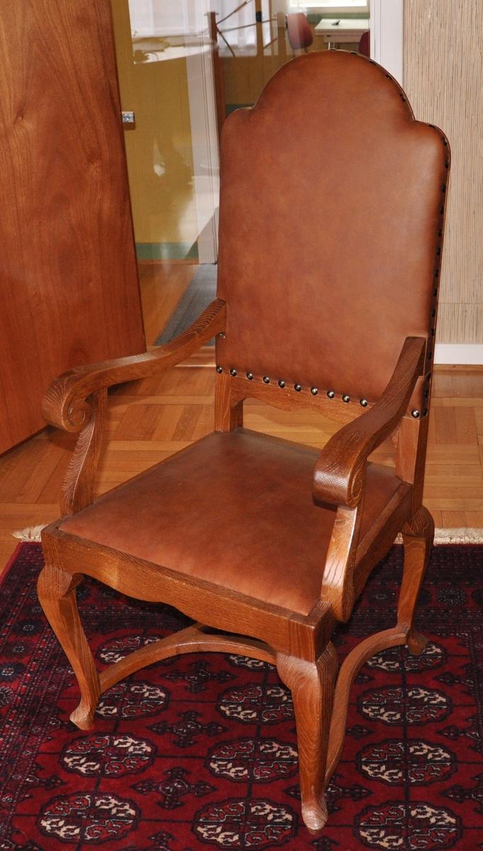 Stol av tre, med skinntrekk. Stolen har skinntrekk på rygg og sete, på ryggen er skinnet festet med nagler med store hoder. Stolen har fire kurvede bein, med h-formet kurvet sprosse. Armlenene har volutt i enden. Sargene er sveifet.