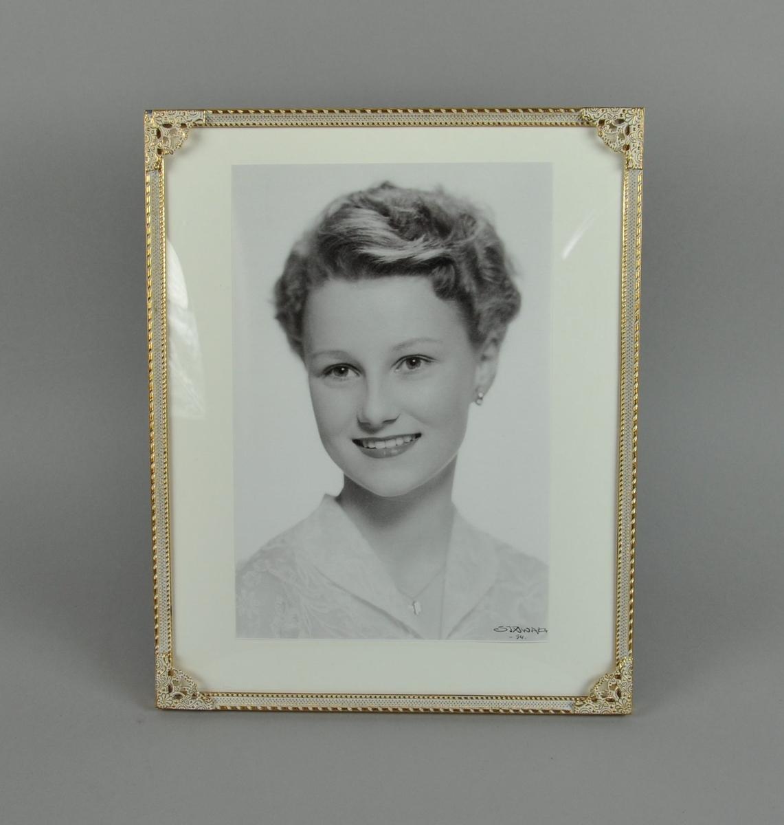 Stående portrettfotografi av H.M. dronning Sonja. Rammen har dekorative border og hjørner og er gullforgylt.