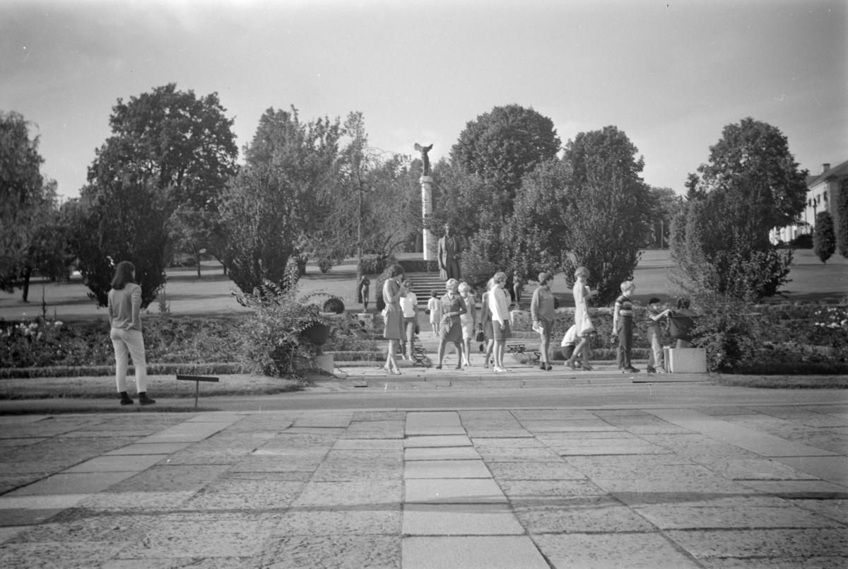 Ungdomblant, antakelig klasse fra Lillehammer husmorskole,  foran en park med monumenter