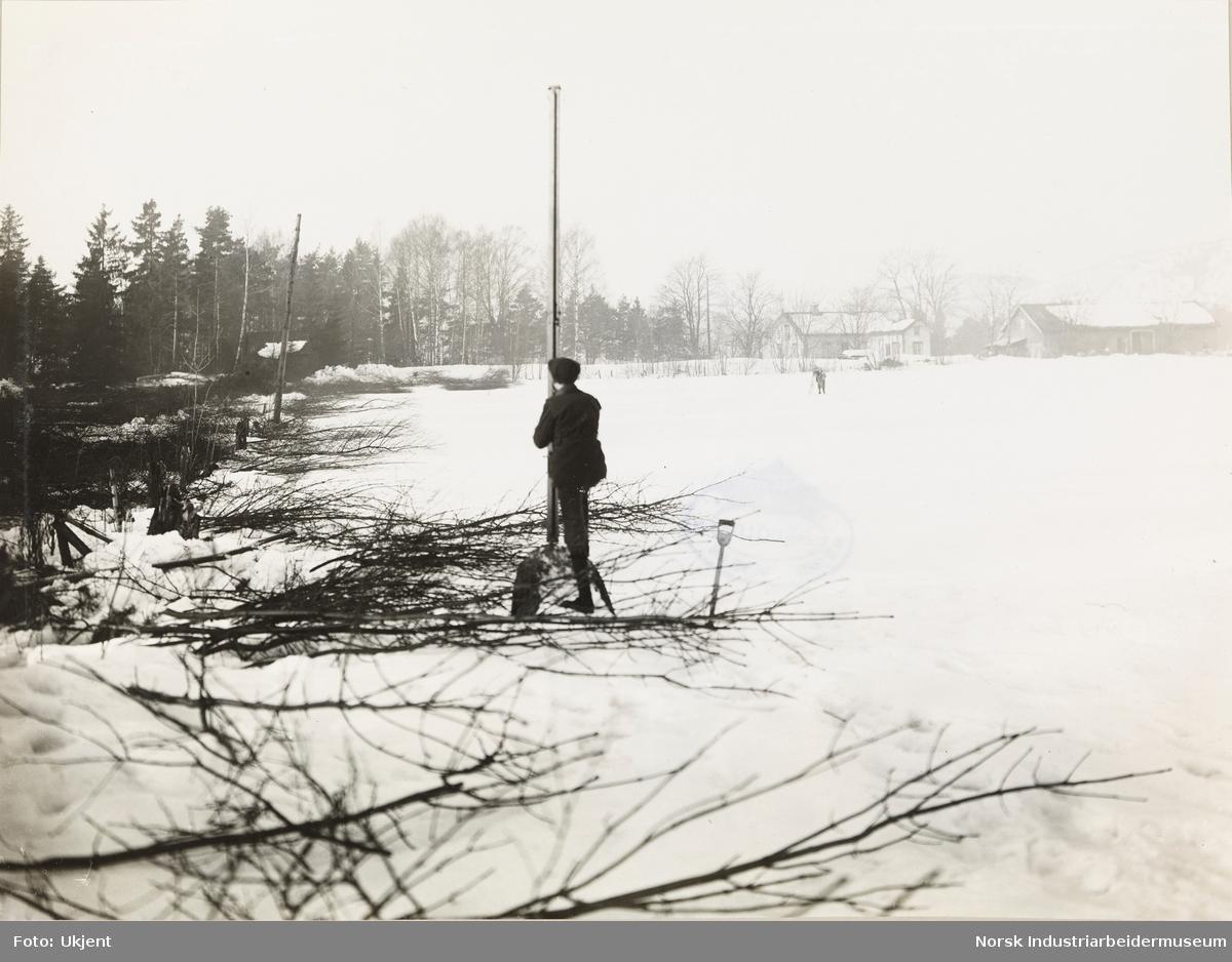 Mann i snødekket landskap ved stolpe. Antatt: det første lysanlegg
