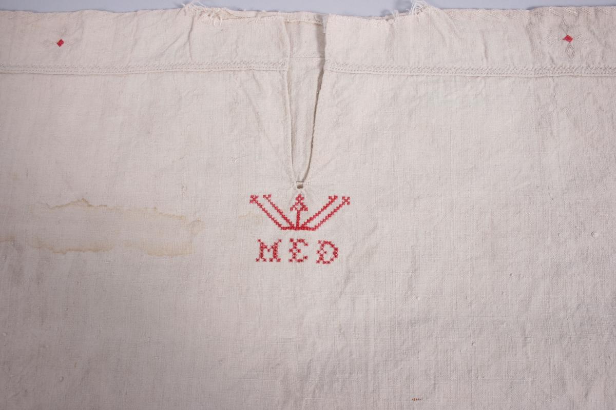 Plagget har bærestykke med broderi i hvitt og rødt. Splitt MF med en regels i bunnen og brodert krone og initialer under. Ermene er isydde med 5 små legg mot fram- og bakstykkene. Ermene er tett rynket mot ermlinningene som har broderier i hvitt og rødt. Trådrester rundt halsrigning og nedre kant på plagget kan tyde på at det har vært en krave/linning i halsen og plagget kan ha hatt en annen stofftype på nedre del.