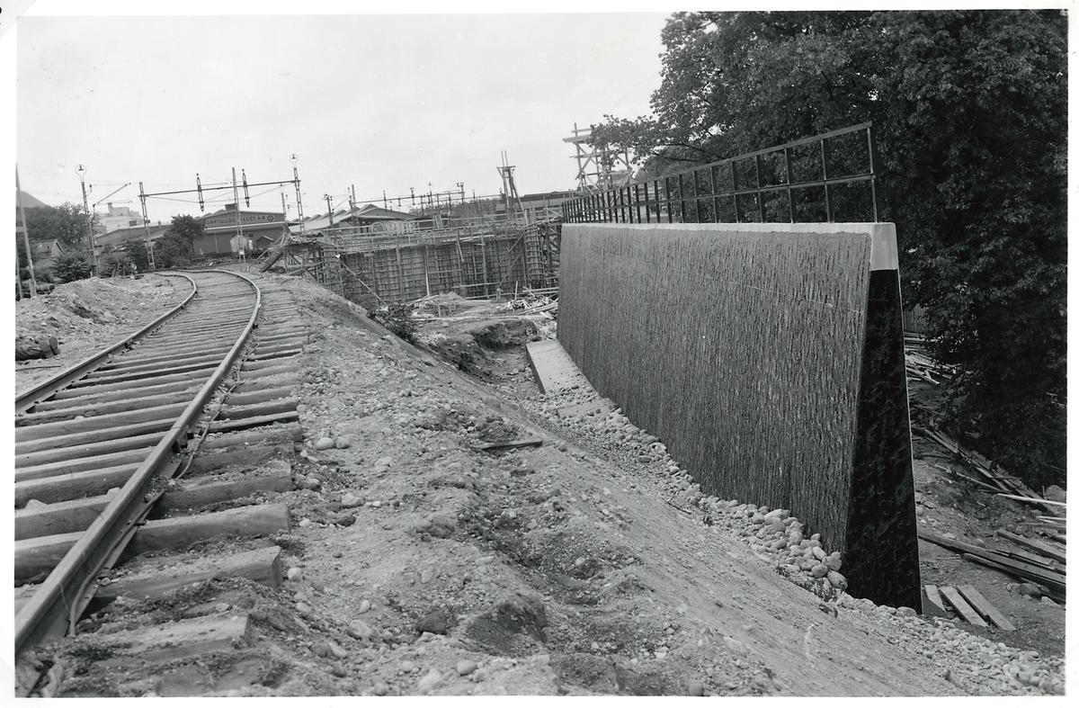 Uppförande av stödmur för järnvägsbanken vid byggnationen av ny järnvägsviadukt över Norrtullsgatan. Belägen ca 100 m öster om östra landfästet i nya vidaukten. Fyllningen bakom muren pågår.