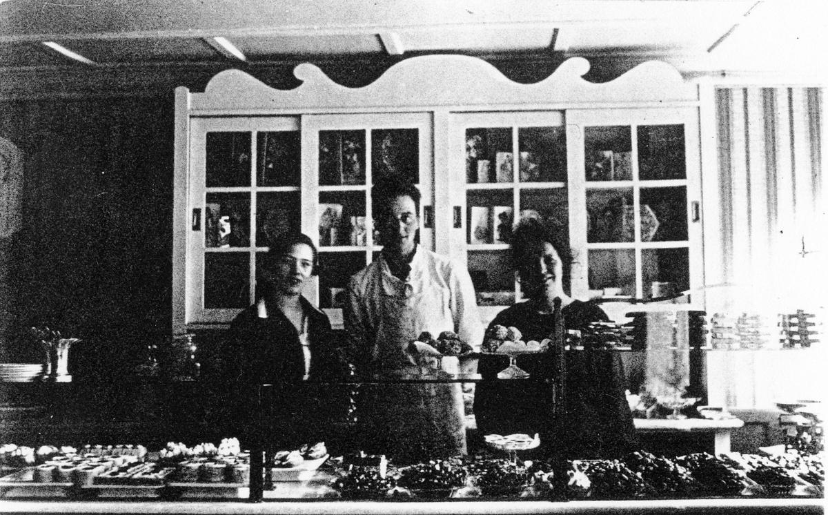 Bild tagen inifrån Ljungblads konditori. Bakom disken, med ett stort urval av konfektyrer, står 2 kvinnor och 1 man.  Från vänster möjligen Judit Ljungblad, gift med Axel Ljungblad, född Andersson.