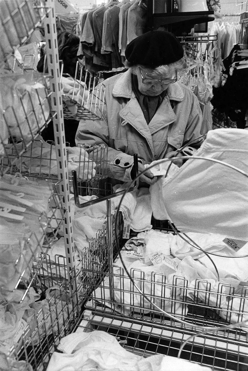 En kvinna tittar på kläder inne på Lindex, Kungsgatan 32, kvarter Pärlan 7. I november 1990 flyttade butiken tillsammans med Gulins (senare Adelsten) in i Epas gamla varuhus i kvarter Storken 12.