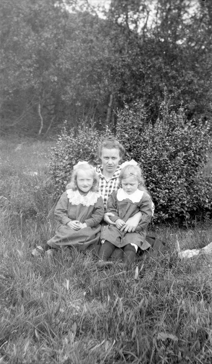 Gruppeportrett av kvinne med to barn sittende ute.