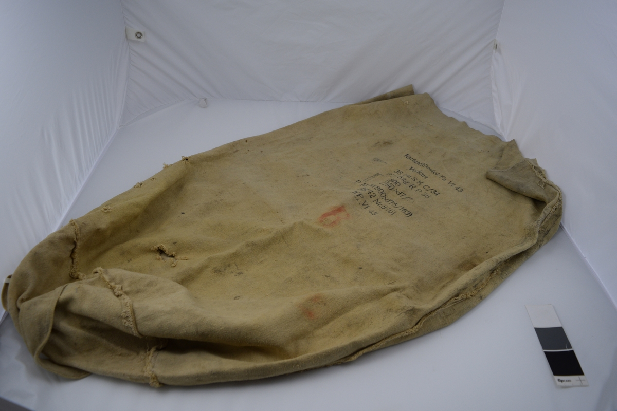 Original karduspose for drivladning tilhørende til 38 cm SK C/34 kanon på Møvig Fort. Sylindrisk form av et stykke med påsydd rundt bunn. To påsydde handtak. Håndsydde sting langs toppen.