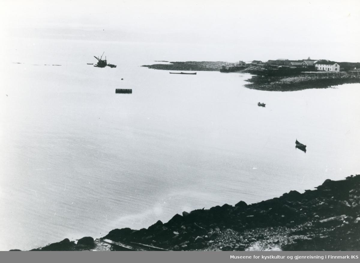 Nordvågen. Holmen med våningshus, kaianlegg og fiskehjeller sett fra Vestersia. Båter på havet. T.v. mudring av skipsleia. 1908.