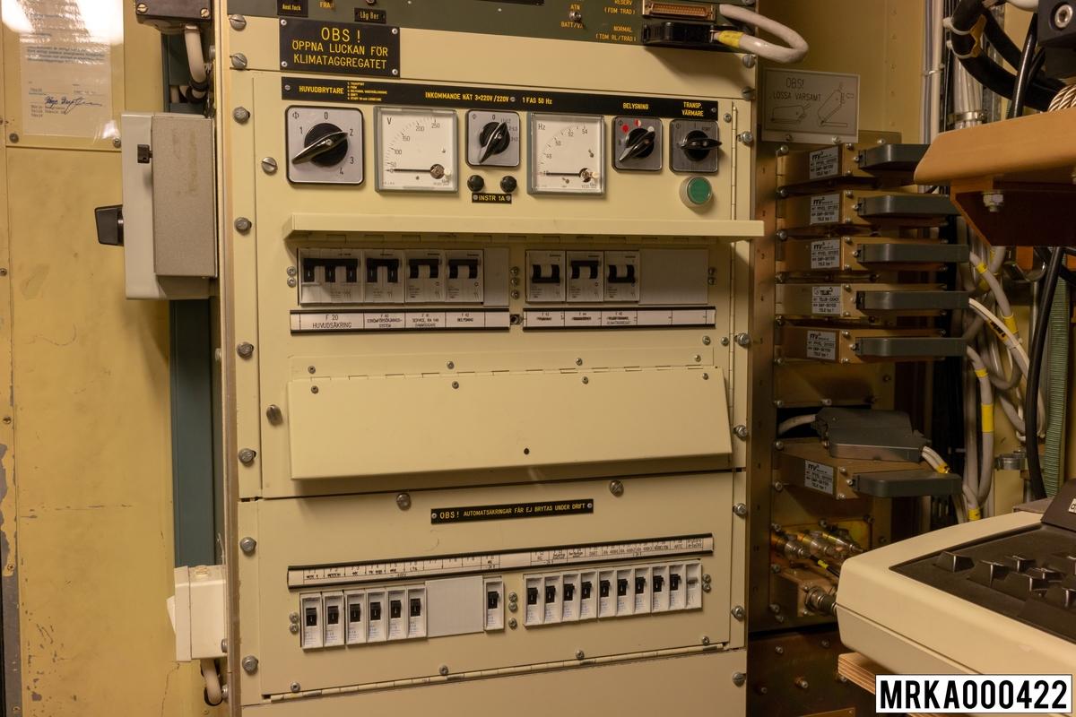 Stativ 1 består av larmenhet, omkopplingspaneler, elcentral 220 V, 24 V, 48 V och kopplingsenhet. 220 V-systemet matas med 3x220 V från ett fristående elverk 16 kVA. 220 V-systemet används för strömförsörjning av eldledningsutrustning, sambandsutrustning, belysning, fläktar, radiatorer, tilluftkanal och klimataggregat. 24 V, 48 V-systemet används för strömförsörjning av övrig sambandsutrustning, nödbelysning och transportvärmare.
