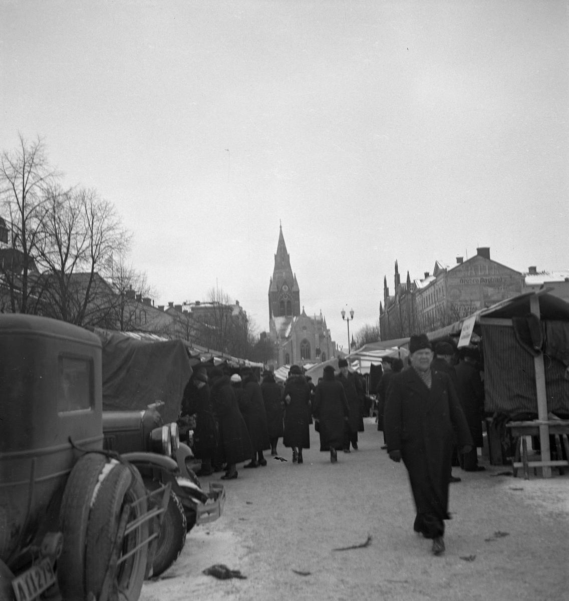 Hindersmässan i Örebro den 28 januari 1937. Människor promenerar mellan marknadsstånden på östra delen av Stortorget. Nikolaikyrkan syns i bakgrunden.