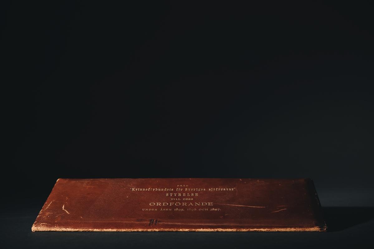 """Läderetui med 16 medaljer med kvinnoporträtt i följande ordning (enligt maskinskrivet ark liggandes löst): """"Styrelsen för Kvinnoförbundet för Sveriges Sjöförsvar 1895-1897"""" 1. Amiralinnan Christersson 2. Fru Anna Wallenberg 3. Fru Coralie Elliot 4. Fru Landshöfdingsk. Emma Dyrssen, f. Fock 5. Fru Juel f. Björkman 6. Fru Hildegard Elliot f. Stråhle 7. Fru Ebba v. Eckerman f. Grevinnan v. Hallwyl 8. Fru Lannerstierna f. Almgren 9. Grevinnan Lotten Hamilton f. Beck-Friis 10. Fru Charlotte Wessäll f. Lewnhaupt 11. (tomt) 12. Fru Ida Carlstedt 13. (tomt) 14. Fru Wrangel f. Hallberg 15. Friherrinnan Ingeborg Hermelin f. Strömberg 16. (tomt)"""