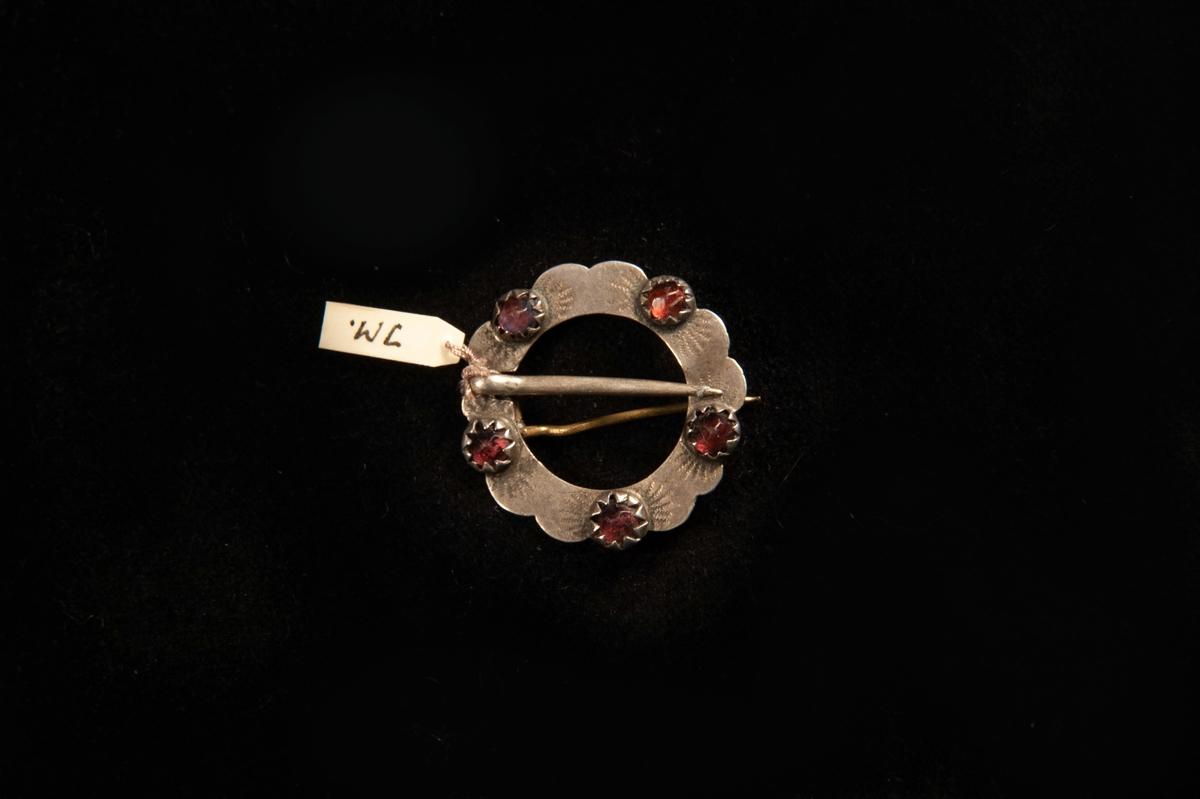 Ett runt spänne av silver med graverad dekor runt 5 infattade röda stenar av glas. Omgjord till brosch. Stämplar bakpå.