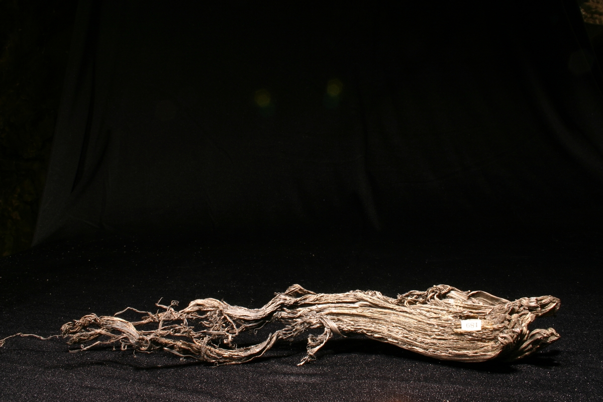 Etikett: 189 Vekt: 247,36 g Størrelse: 31 x 5 x 3,5 cm Avbildet i Carl Bugge (1917) Kongsbergfeltets geologi. NGU Nr. 82. Fot. 20. Sølvtrådene er mer sammenpresset i dag enn på Bugges foto.