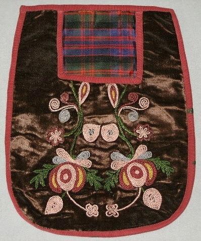 Väska i brun sammet med kedjestygnsbroderi. Foder oblekt linneväv., synligt rutigt sidenfoder.Baksida av brunt bomullstyg.Kantad med rostbrunt bomullsband.
