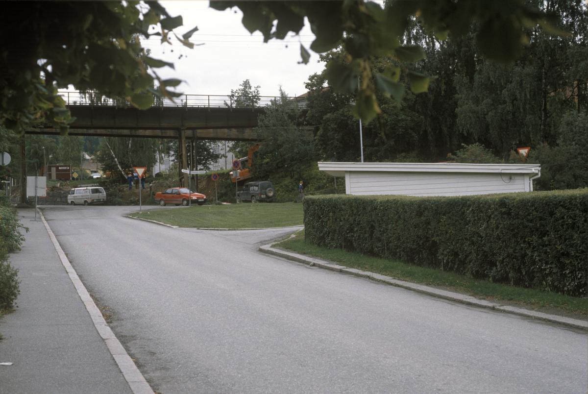 Lillehammer. Øverst del av Sorgendalsvegen. Kryss med Bryggevegen i forgrunnen. Den kvite garasjen til høyre tilhørte Sorgendalsvegen 2A. Avkjøringer til Bryggevegen bak denne. Før utbygging av Mesnadalsvegen. Jernbanebrua i bakgrunnen. Sett mot øst.