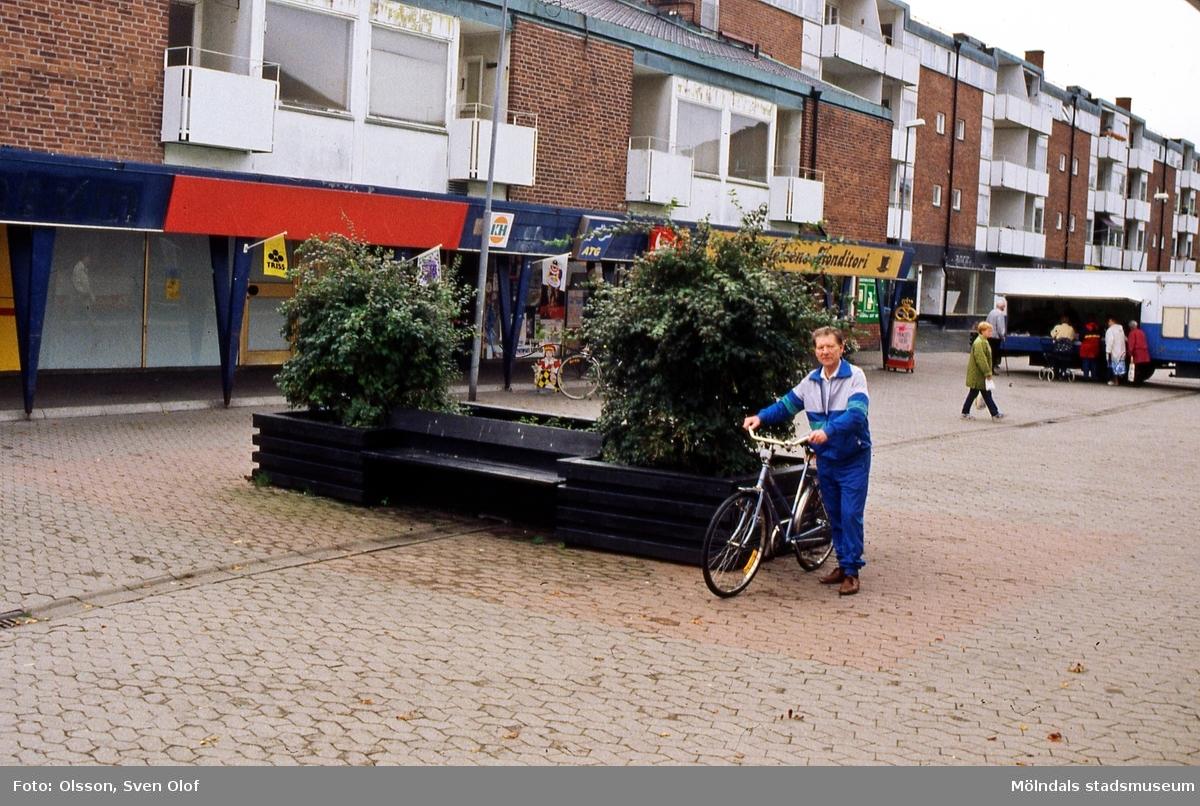 En man leder sin cykel över Jungfruplatsen i Mölndal, oktober 1998. Närmast ses huset Jungfruplatsen 1. Konsum har stängt. Posten, tobaksaffären och fotoaffären har också stängt. D 30:9.