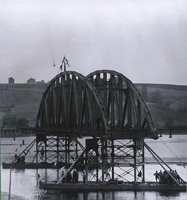 Gammelt foto av del av bro som slepes på prammer.