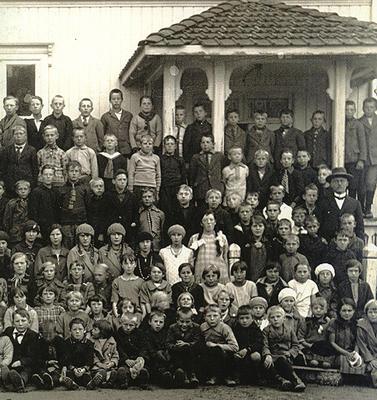 Gammelt foto av skolebarn og lærer oppstilt foran skolebygning.
