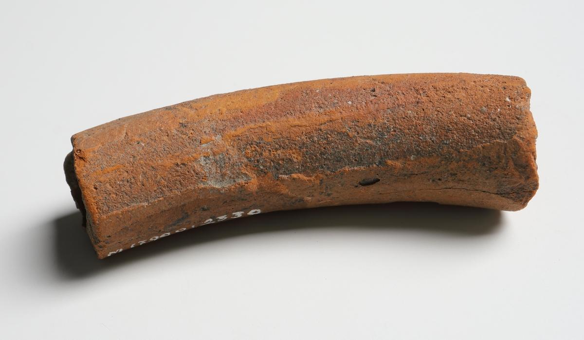 Del av ett ihålig snurrat horn (blåsinstrument). Cylindriskt rör med lätt böjd form. Yngre rödgods. Tillverkad i den tyska staden Lübeck eller södra delarna av Schleswieg-Holstein under 1500 - 1600-talet. (Se Referenser/Digitala objekt för liknande objekt av stengods).