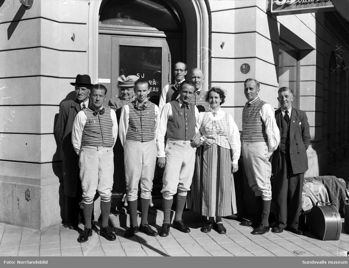 En grupp spelmän på resa. Bilden är tagen utanför SJ resebyrå i hörnet av Bankgatan och Rådhusgatan.