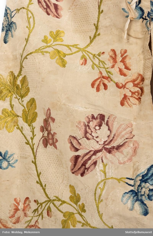 Dåpskjolen er sydd av en tidligere dåpspose (løyert). Ved omsying til kjole er hetten tatt av og stoffet benyttet til ermer. Den er sydd av 1700-talls silkebrokade. Sannsynligvis engelsk/ Spitalfield. Design Anna Maria Garthwait, Den opprinnelige dåpsposen er foret med ubleket bomull (eller baskerlin). Ved omsyring til kjole er overdelen fôret med rød bomull. Det er sydd tre løpeganger i overdelen. Her er tredd inn bomullsnorer til å knytte kjolen sammen. Ermene er påsydd kniplinger ved ermeåpningen.  Giveren opplyser at stoffet ble brukt i brudekjolen til hennes tipp-tippoldemor.