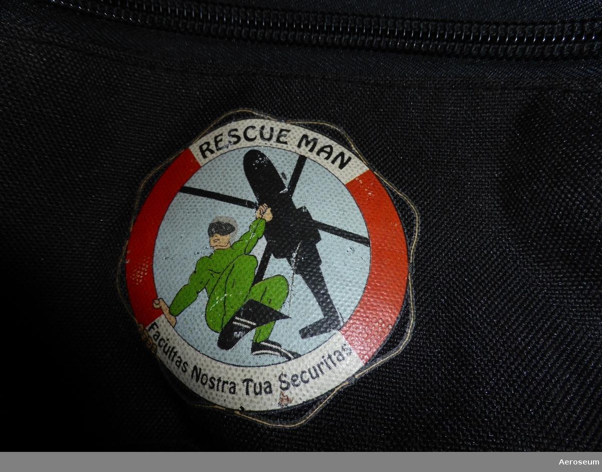 """En transportväska som är gul och svart. På väskan finns det ett tryckt emblem i form av en livboj med en bild på en ytbärgare. Runt bilden står det: Rescue Man facultas Nostra tua Securitas"""". Det finns också en påstruken vit text: """"rescue man helicopter wing""""  Väskan är försedd med hjul."""