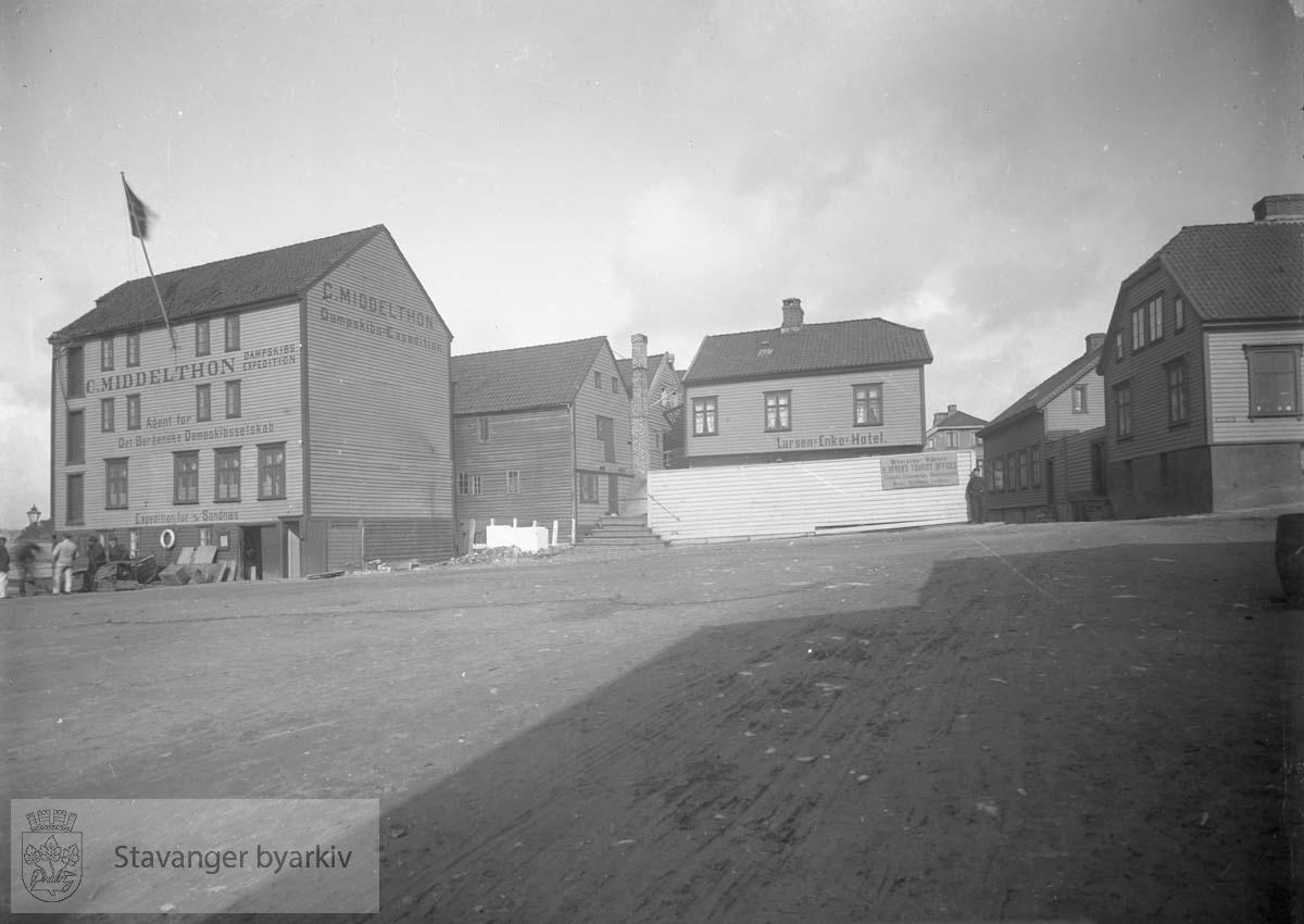 Til venstre: Skansegaten 15, C. Middelthons sjøhus og dampskipsekspedisjon. På hjørnetomten midt i bildet ble C. Middelthons murbygning Skansegaten 13 reist i 1897. Huset midt i bildet, Nordbøgaten 4, er Larsens Enkes Hotel. De to husene til høyre er Baadegaten 10 og Skansegaten 11.