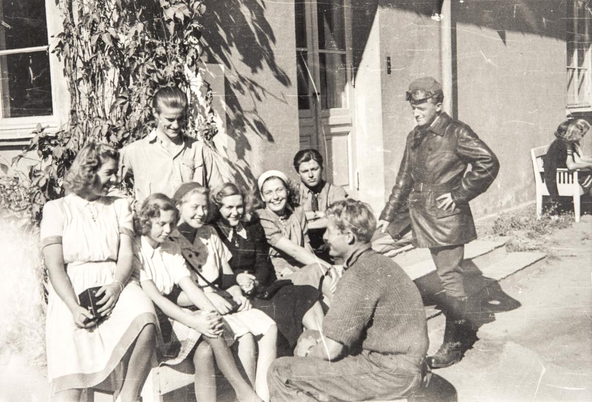 Norske polititropper står sammen med en gruppe kvinnelige sivile utenfor et hus, våren 1945.