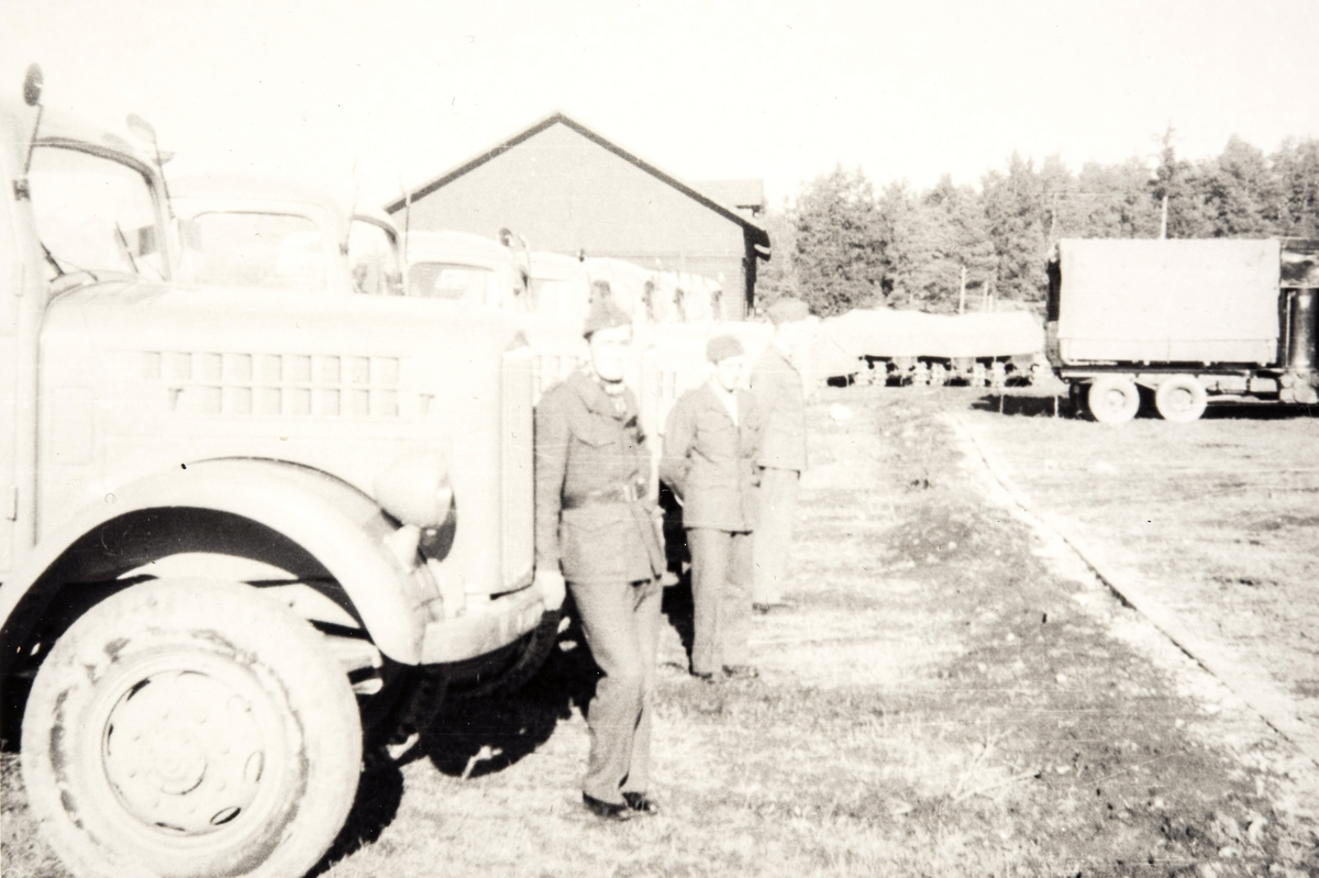 Prospektfotografi av en militærforlegning på Blindern med militære kjøretøy stående utenfor. Fremfor bilene står 3 troppsoldater.