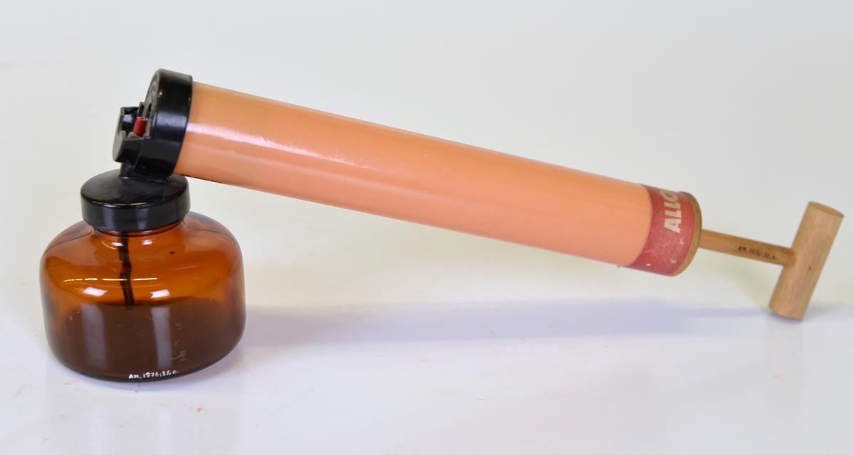 Insektsspruta bestående av A: trähandtag, B: rör, orangefärgat, C: behållare av brunfärgat glas. Märke: ALLOMAL