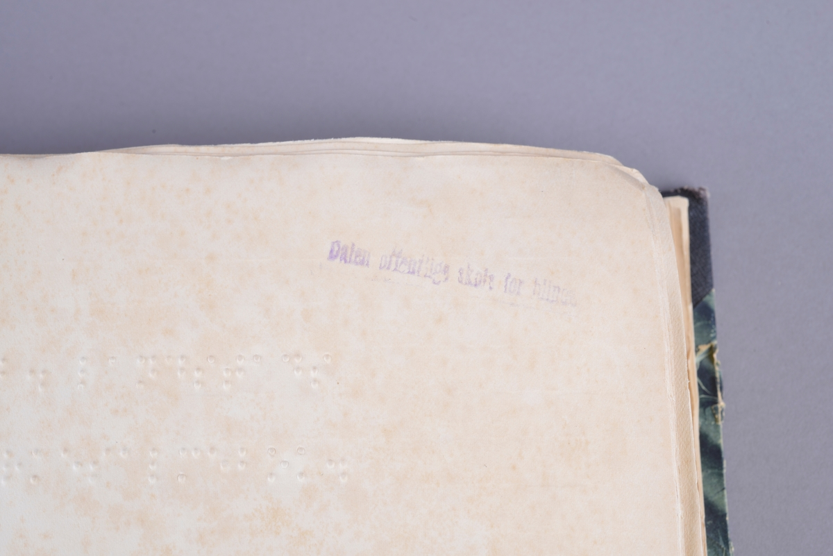 Bok med noter og tekst i punktskrift. Ensidig trykk på hvitt papir. Forsatsen har noe brunere papir og grønt mønstret dekor. Stive permer. Grønt marmorert omslag.  Halvbind. Ryggen og hjørnene er forsterket med svart lerret.