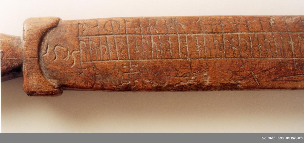 KLM 7773  Runstav, av trä. Platt fyrsidig med svärdfästliknande handtag och doppsko av järn. Kalendern uppritad på bredsidorna. På ena bredsidan närmast handtaget årtalet 1515.