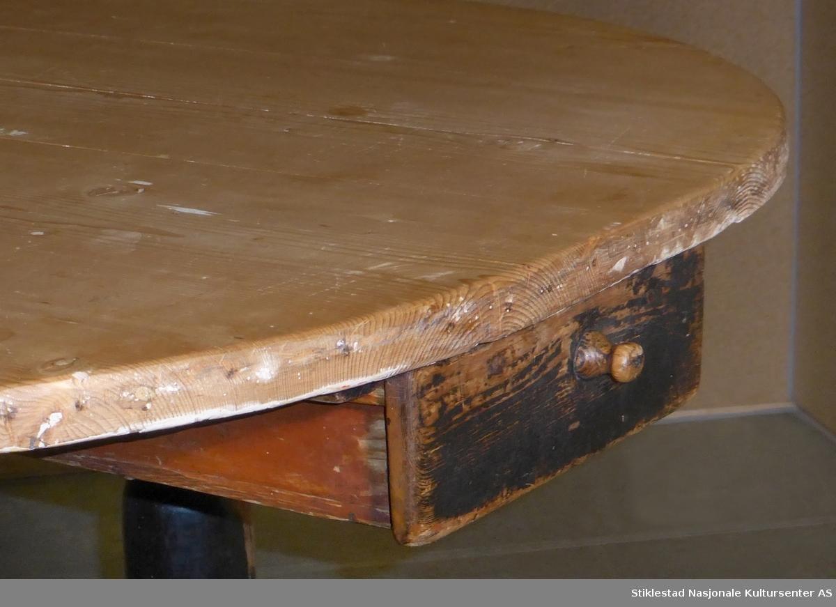 Stort kjøkkenbord med rektangulær ufarget bordplate med buede hjørner. Bordet har svart uprofilert sarg og profilert fotlist, dreide føtter. På ene langside har bordet en bred skuff. Det er montert en liten skuff på ene kortside, denne er montert under selve bordplata. Fotlisten er spesielt slitt på hver langside. Bordet består av 4 deler.