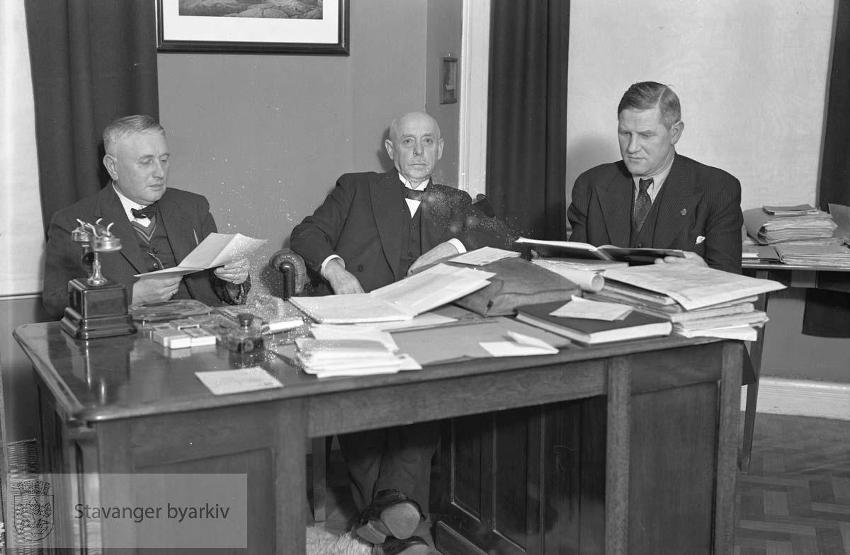 Tre menn ved skrivebord.