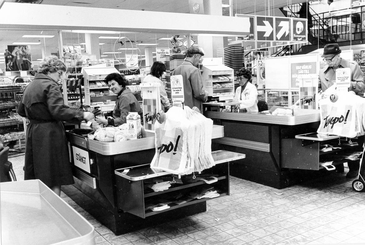 Butiksinteriör, på bilden ses kassaavdelningen med betalande kunder och butikspersonal.