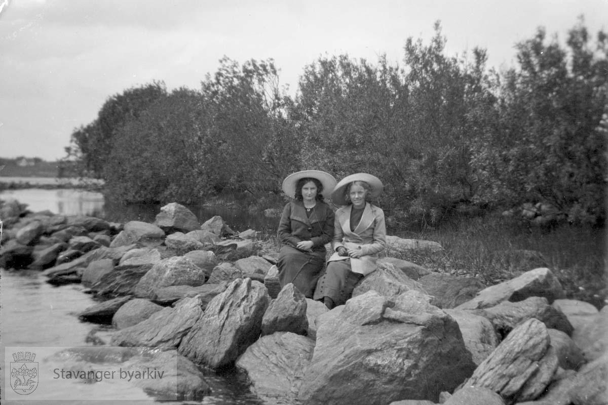 To kvinner med hatt på steiner langs vannkanten