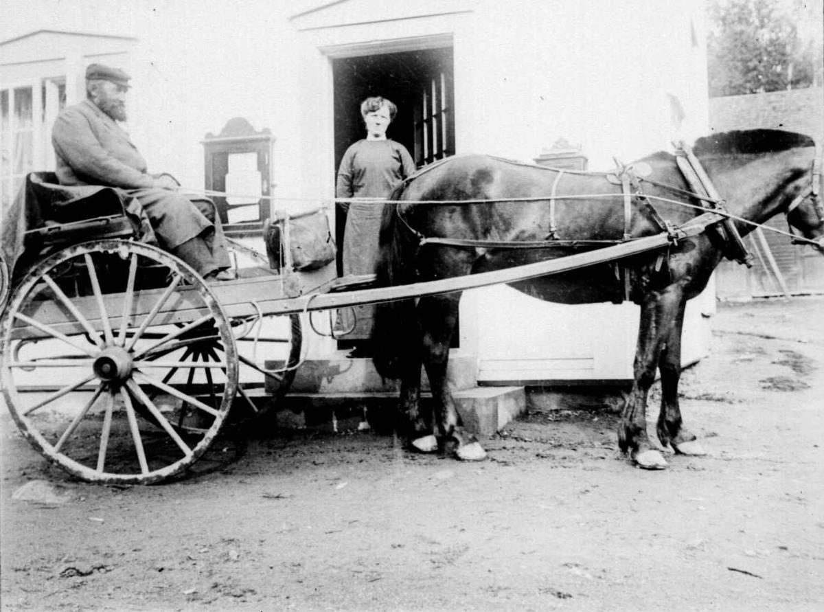 Postmann Andersen i hest og kjerre utenfor antatt butikk med oppslagstavle