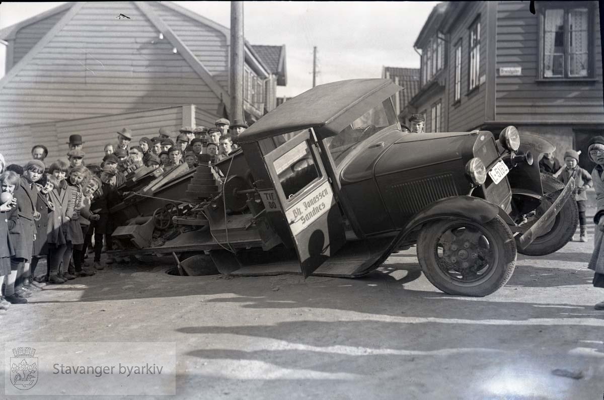 Trafikkulykke i Brønngaten. En lastebil fra Bh. Jonassen, Sandnes, har kjørt nedi en åpen kum. De skuelystne er på plass.