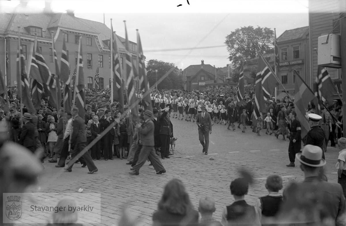 Folk i tog.Nasjonal Samling (NS).Unghirden kommer marsjerende ned Olavskleiva bak i bildet
