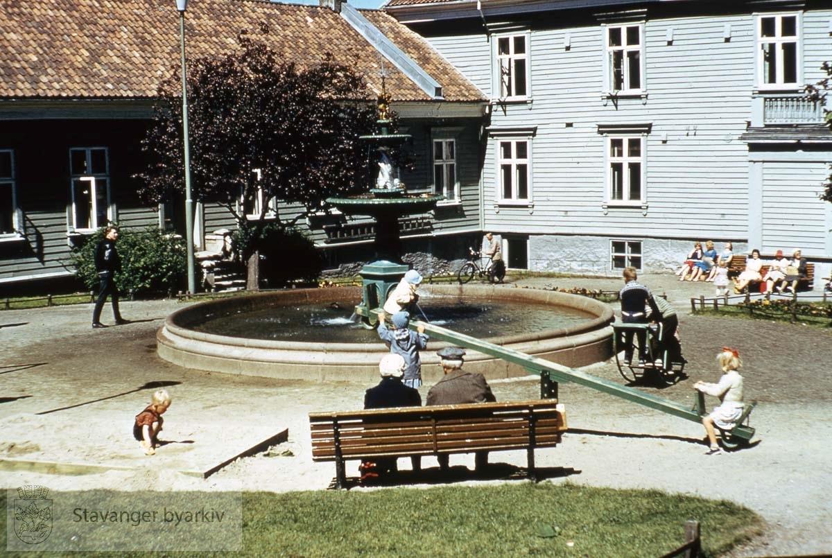 Lekeplass ved fontenen...Fontenen erstattet Mortepumpen på Torget da denne ble fjernet i 1865. I 1897 ble den flyttet til St. Petri plass ved kommuneadministrasjonen. Da disse byggene ble revet i 1963, ble den flyttet til Johannesparken. Siden 1985 har den stått utenfor Rosenkildehuset.