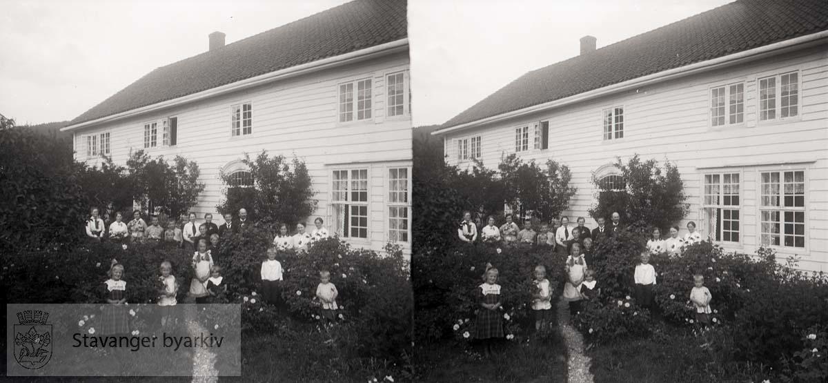 Stort besøk i Gloppen hos sogneprest Kristian Martin Eckhoff og hans hustru Karen Mathea Smith. Del av slekta Eckhoff og Smith har stilt seg opp i hagen til Indre Vereide prestegard i Gloppen hvis hovedhus ble oppført i 1782...Stereofotografi.