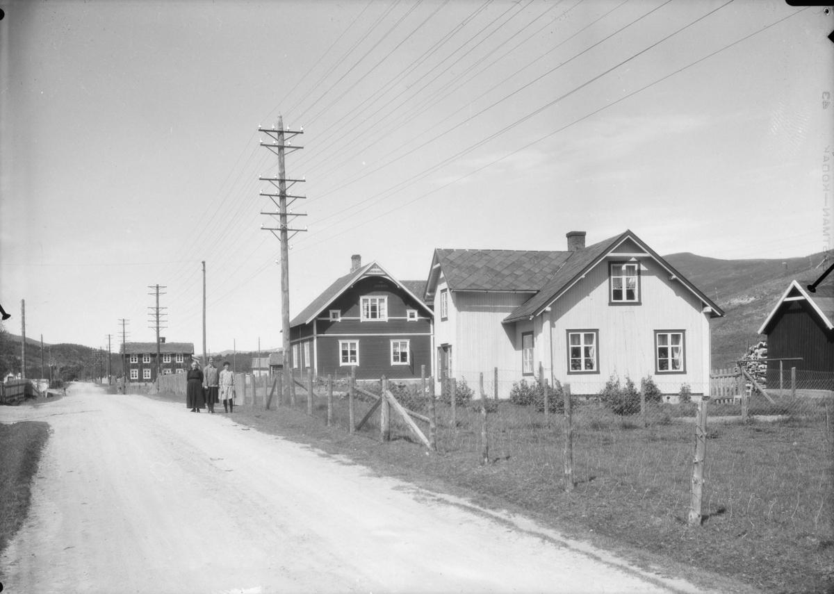 Bebyggelse ved Marøy, Kongsvegen, Dovre. Fra høyre Heimly, hjemmet til Kari Hattrem som står i mørk kjole. Så Nordheim og helt bak i bilde Øyom som eides av Anna og Peder Bagås. Har vært kafe og butikk der.