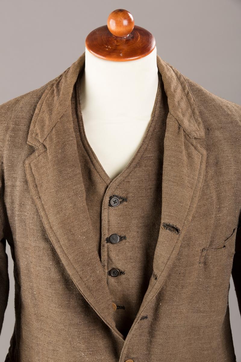 Form: Liten krage, små slag, 5 knapper, lomme med klaff på hver side, utvendig brystlomme, innelomme. Foret med bomull.