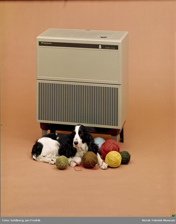 En svart og hvit hund, av rasen cocker spaniel, ligger foran en varmeovn fra Husqvarna. Rundt hunden ligger flere garnnøster i forskjellige farger.